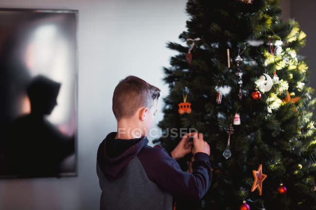 Side view of boy putting up Christmas decorations — Stock Photo