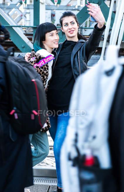 Deux jeunes femmes en selfie sur une passerelle du millénaire, Londres, Royaume-Uni — Photo de stock