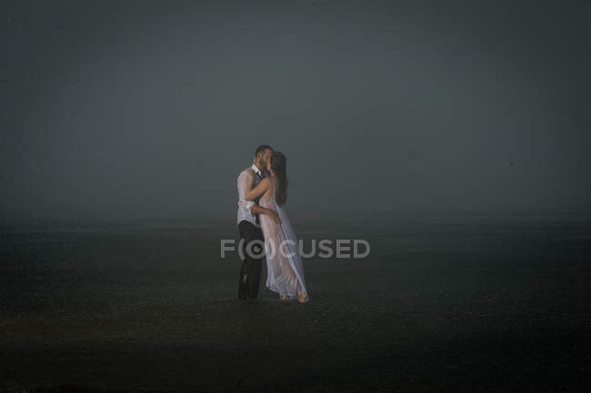 Wet couple kissing on misty beach — Stock Photo