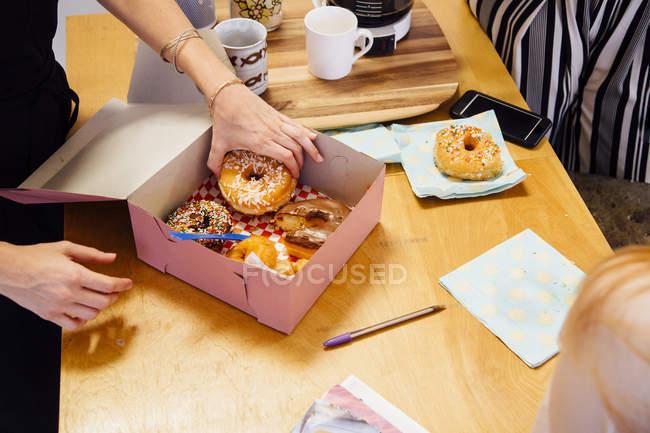 Обрезанное изображение женщины, кладущей пончики в коробку с тортами — стоковое фото