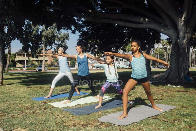 Школьницы практикующие йогу воин позируют на школьном спортивном поле — стоковое фото