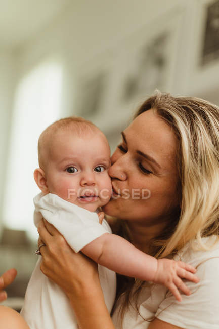 Donna baciare figlia bambino sulla guancia — Foto stock