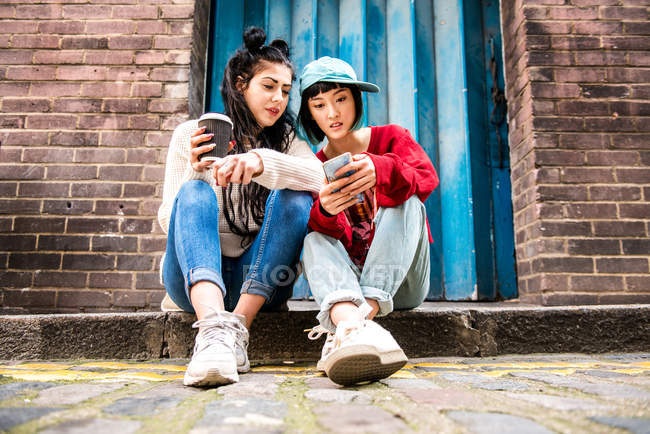 Two young women sitting on sidewalk and looking at smartphone — Stock Photo