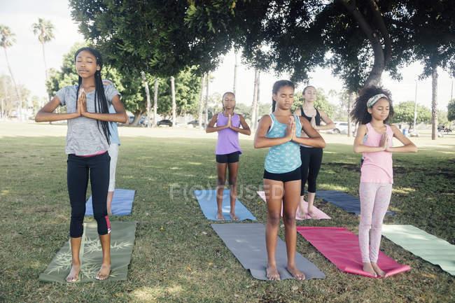 Девочки и школьницы-подростки практикуют йогу в горной позе на школьном игровом поле — стоковое фото