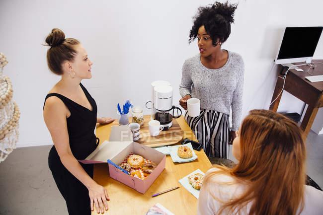 Коллеги порвали с кофе и коробкой пончиков — стоковое фото