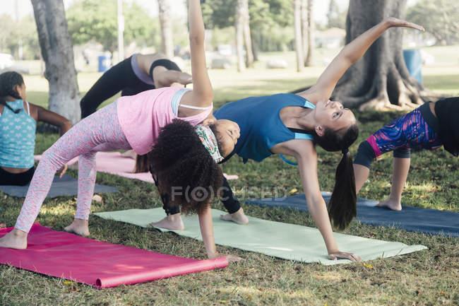 Школьницы, практикующие йогу, позируют на школьном игровом поле — стоковое фото