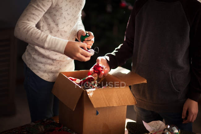 Cropped view of brother and sister putting up Christmas decorations — Stock Photo