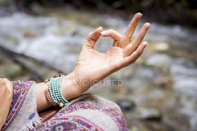 Крупный план молодой женщины, медитирующей у реки — стоковое фото