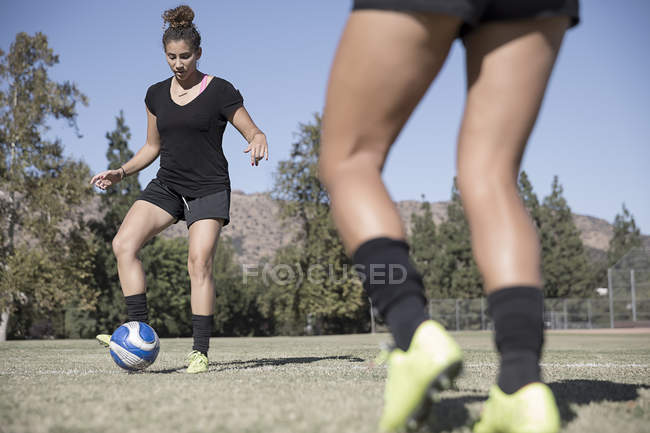 Women playing football on soccer pitch — Stock Photo