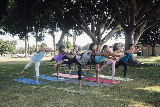 Школьницы практикующие йогу воин три позы на школьном спортивном поле — стоковое фото