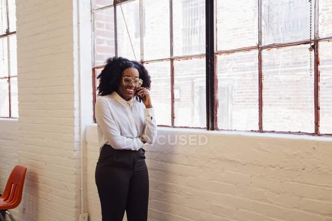Mujer haciendo una llamada telefónica en la oficina - foto de stock