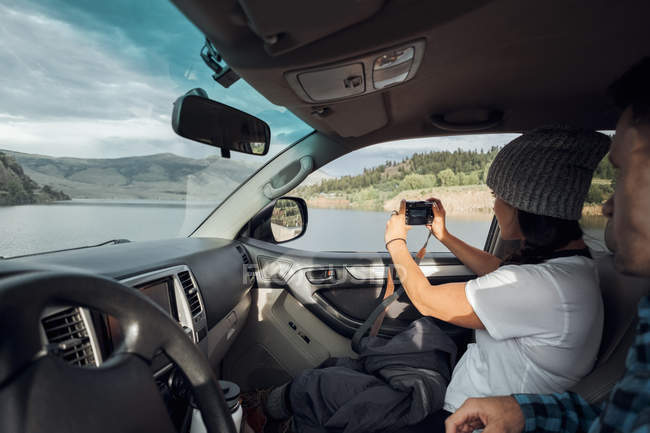 Couple in car, young woman taking photograph through car window, Silverthorne, Colorado, USA — Stock Photo
