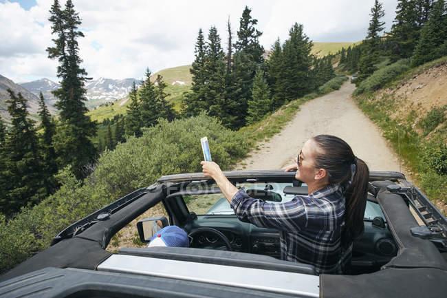 Young woman on road trip taking smartphone selfie travelling in convertible, Breckenridge, Colorado, USA — Stock Photo
