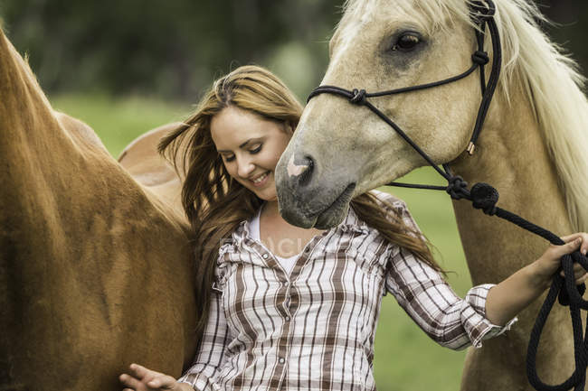 Young woman walking with two horses, smiling — Stock Photo