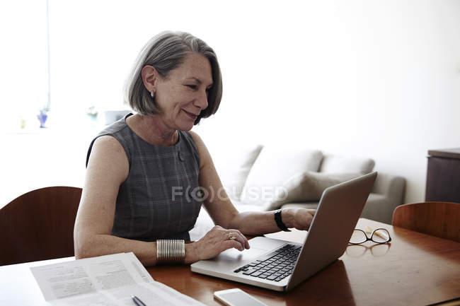 Старшого бізнес-леді сидячи за столом, використовуючи ноутбук, посміхаючись — стокове фото