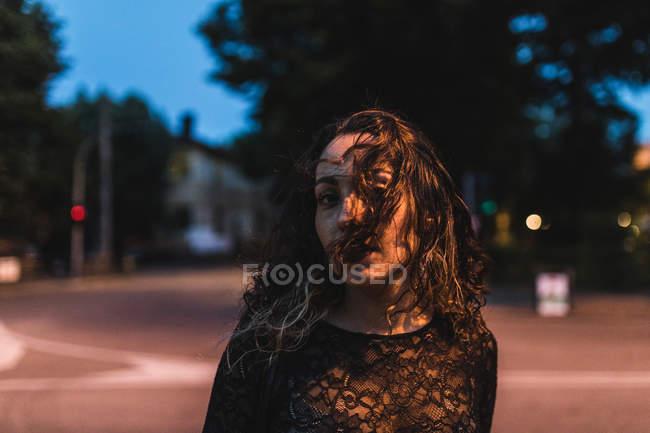 Портрет жінка в місті вночі, волоссям прикривши обличчя — стокове фото