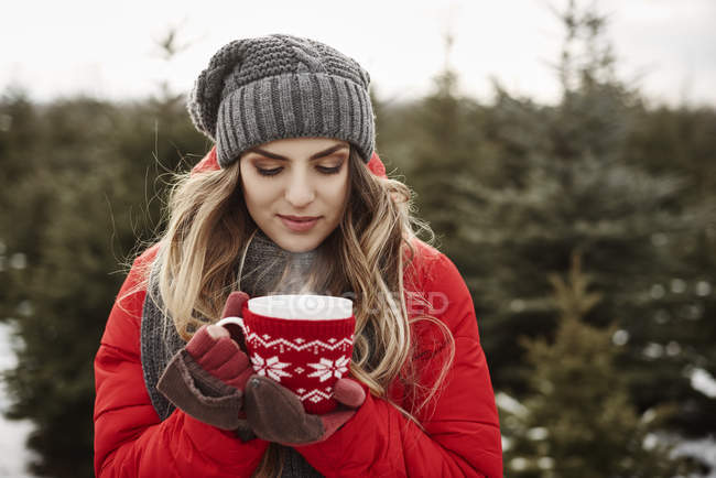 Portrait of young woman with coffee in christmas tree forest — Stock Photo