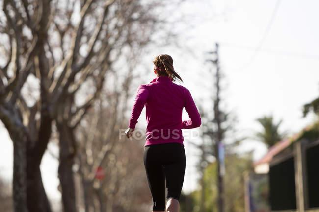 Vue arrière de la jeune femme jogging — Photo de stock