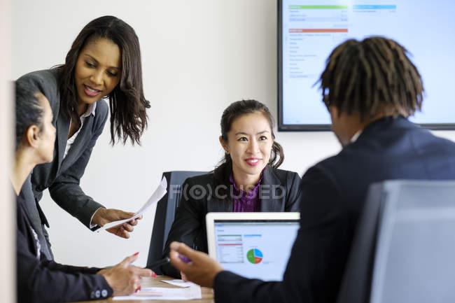 Homme d'affaires et femmes d'affaires utilisant un ordinateur portable au bureau — Photo de stock