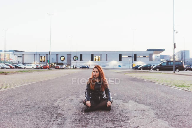 Red haired woman sitting with cross legged in car park — Stock Photo
