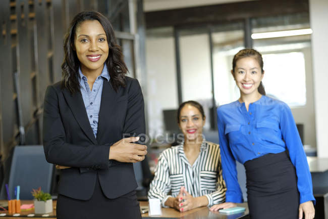 Portrait of three businesswomen in open plan office smiling at camera — Stock Photo