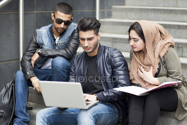 Three friends sitting on steps and looking at laptop — Stock Photo
