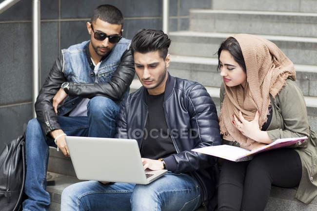 Tre amici che si siedono sui gradini ed esaminando computer portatile — Foto stock