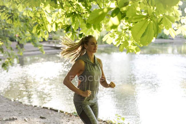 Jeune femme au bord du lac dans le parc — Photo de stock