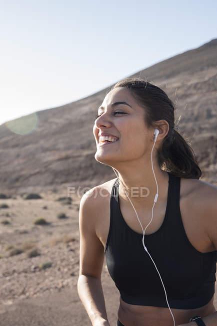 Jovem feliz corredor feminino em fones de ouvido em paisagem árida — Fotografia de Stock