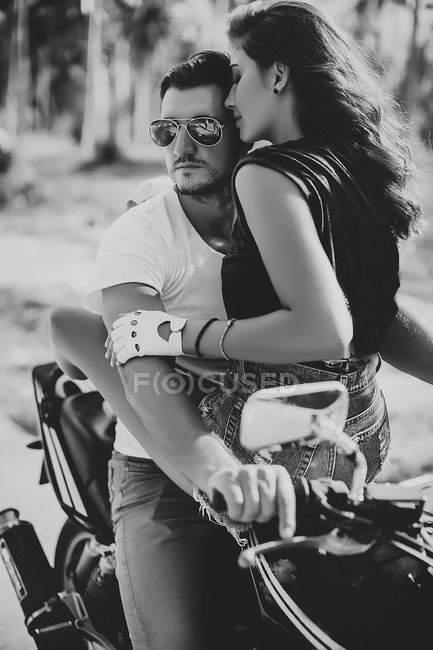 Mujer joven abrazando novio en motocicleta - foto de stock