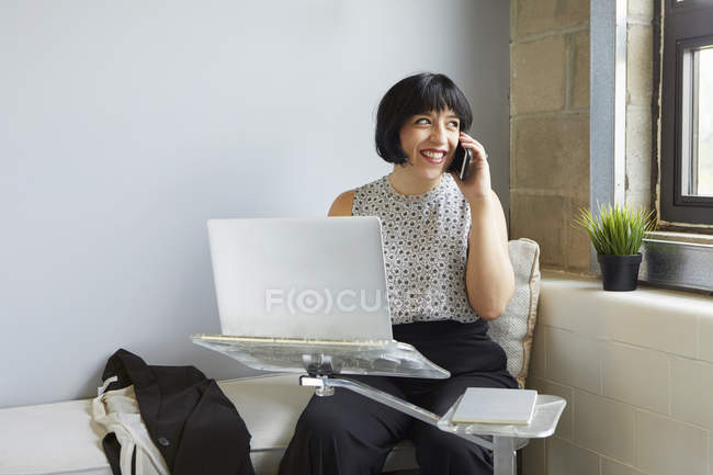 Mulher usando laptop e falando no smartphone — Fotografia de Stock
