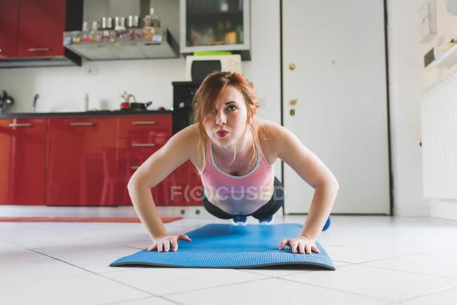 Porträt der jungen Frau tun Push ups auf Küchenboden — Stockfoto