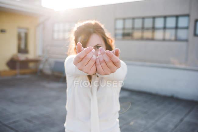 Porträt der jungen Frau mit Hände ausstrecken auf sonnigen Dachterrasse — Stockfoto
