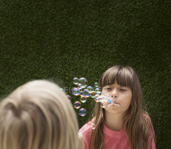 Two Girls blowing bubbles against hedge — Stock Photo