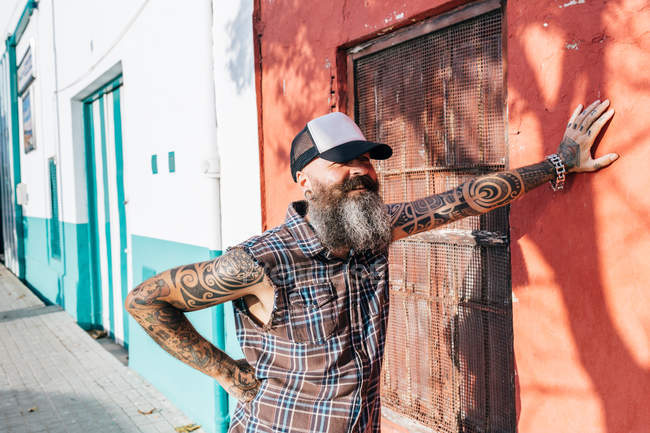 Tattooed male hipster leaning against sunlit wall — Stock Photo