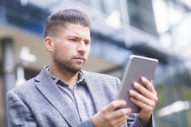 Homem olhando para tablet digital ao ar livre — Fotografia de Stock