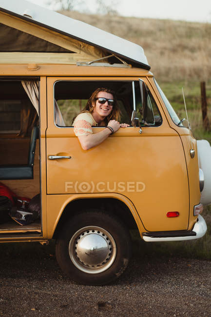 Portrait of long haired young man at vintage vehicle window, Exeter, California, USA — Stock Photo