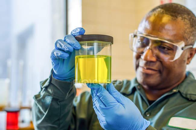 Labortechniker betrachtet Becher mit gelbem Biokraftstoff im Labor einer Biokraftstoffanlage — Stockfoto