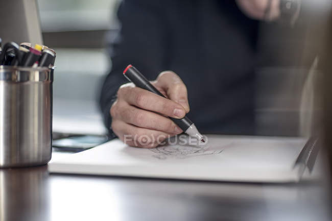 Hand of young male designer drawing at home desk — Stock Photo