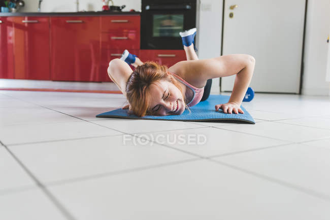 Young woman doing push ups on kitchen floor — Stock Photo