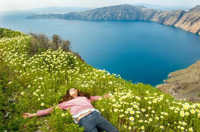 Ragazza sdraiata sul campo di fiori, Santorini, Kikladhes, Grecia — Foto stock
