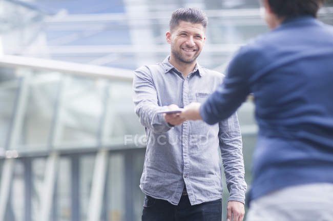 Woman handing smiling young man digital tablet — Stock Photo