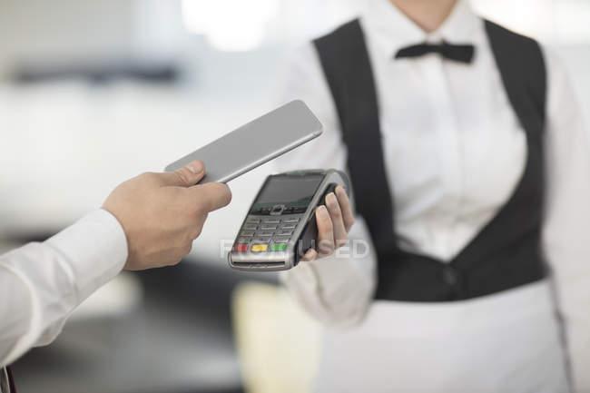 Официантка, проведение оплаты машина сторону клиента, клиент платить бесконтактным методом — стоковое фото