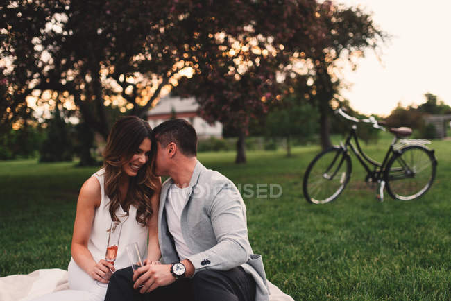 Romantic young couple with pink champagne whispering in park at dusk — Stock Photo