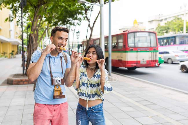 Молодий туристичних пара їдять рожні вуличної їжі на тротуарі, Бангкок, Таїланд — стокове фото