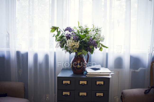 Vase with bouquet of flowers on bedside table by window — Stock Photo
