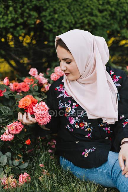 Mujer joven en hijab mirando rosas - foto de stock