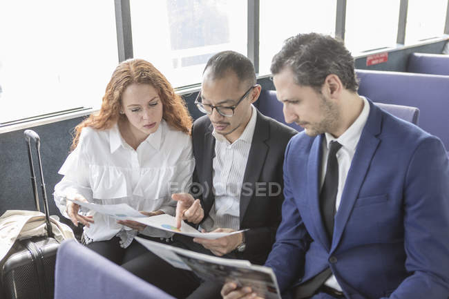 Young businesswoman and businessmen looking at paperwork on passenger ferry — Stock Photo