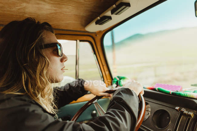 Long haired young man driving vintage vehicle — Stock Photo