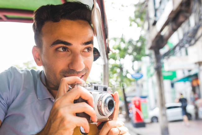 Young male tourist in auto rickshaw with camera, Bangkok, Thailand — Stock Photo